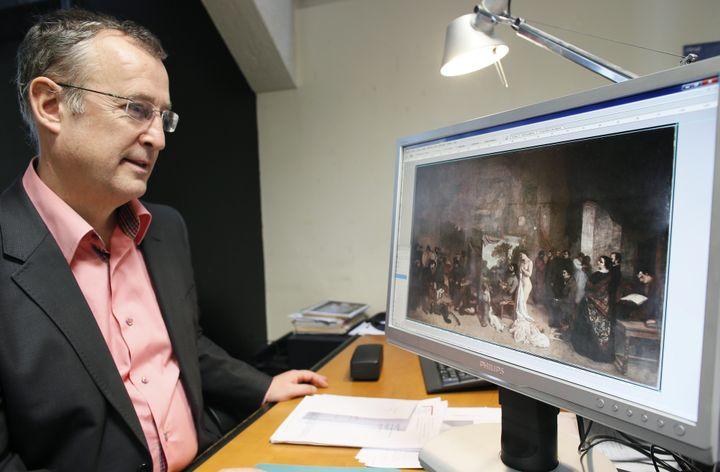 """Bruno Mottin travaillant sur """"L'Atelier du peintre"""" de Courbet  (PATRICK KOVARIK / AFP)"""