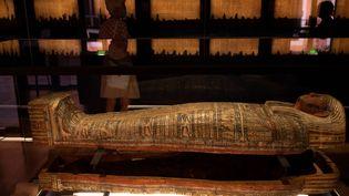 """Des visiteurs observent un sarcophage abritant une momie au musée Granet d'Aix-en-Provence, le 18 septembre 2020 à la veille de l'ouverture officielle de l'exposition """"Pharaon, Osiris et la momie"""" (CHRISTOPHE SIMON / AFP)"""
