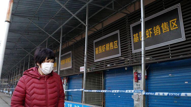 Une femme passant devant le marché de Wuhan (Chine), le 12 janvier 2020. (NOEL CELIS / AFP)