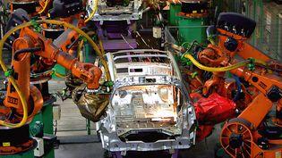 Des robots soudent des éléments d'une carrosserie sur une ligne d'assemblage, le 3 septembre 2004 dans l'usine Renault de Douai (Nord). (PHILIPPE HUGUEN / AFP)