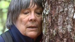 Une promeneuse tente de ressentir les vibrations d'un arbre du sylvaotirum de Mont-Dore (Puy-de-Dôme). (FRANCE 3)
