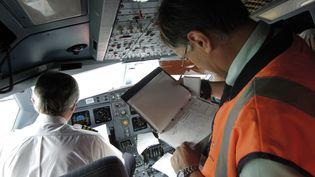 Un pilote de ligne et un contrôleur d'exploitation de la DGAC dans la cabine d'un avion sur le tarmac de l'aéroport Roissy-Charles de Gaulle. (STEPHANE DE SAKUTIN / AFP)