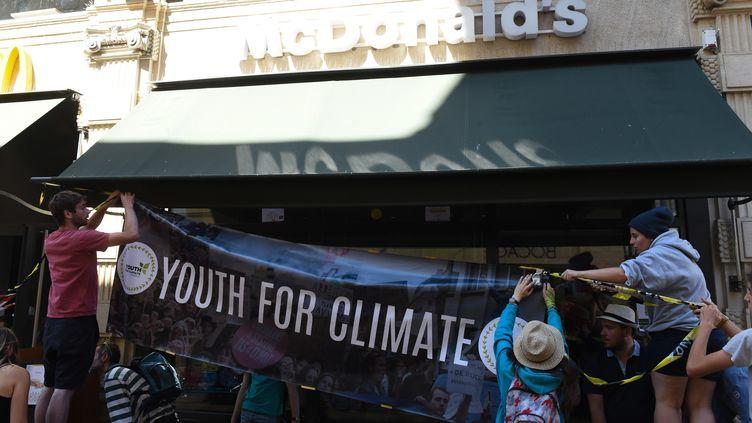 """Des membres de """"Youth for Climate France""""accroche l'une de leurs banderoles sur un restaurant McDonald's de Bordeaux, en juillet 2019. (MEHDI FEDOUACH / AFP)"""