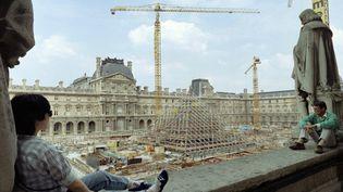 Des touristes observent la construction de la pyramide du Louvre, à Paris, le 7 août 1987. (PATRICK KOVARIK / AFP)