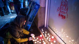 Une femme allume des bougies devant un portrait de Zineb Redouane alors que les gens se rassemblent le 1er décembre 2019 à Marseille pour rendre hommage à la vieille dame. (CLEMENT MAHOUDEAU / AFP)
