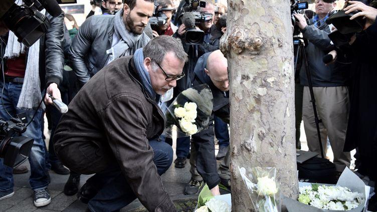 Denis Jacob, secrétaire général du syndicat Alternative police, dépose une gerbe de fleurs sur les Champs-Elysées, à Paris, le 21 avril 2017. (PHILIPPE LOPEZ / AFP)