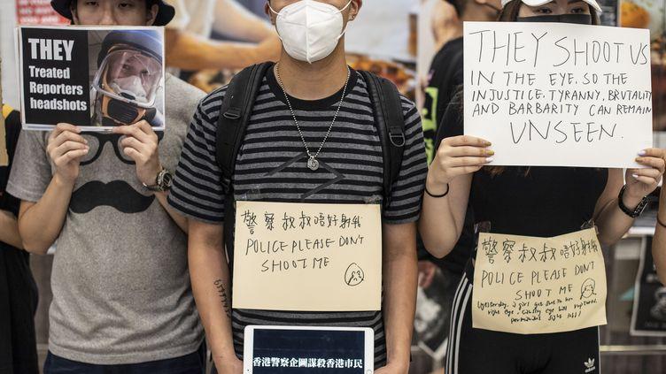 Les manifestants tiennent des pancartes à l'aéroport de Hong Kong, à la suite d'une manifestation, le 12 août 2019. (PHILIP FONG / AFP)