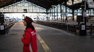 Une cheminote présentepour orienter les voyageurs pendant la grève, dans une gare déserte, le 19 avril 2108 à Paris.  (CHRISTOPHE SIMON / AFP)