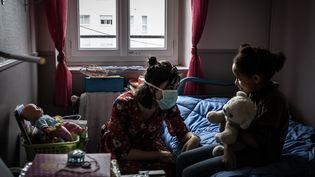 Une éducatrice portant un masque discute avec une petite fille dans un centre social près de Lyon. (JEAN-PHILIPPE KSIAZEK / AFP)