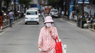 Une femme masquée dans une rue de la ville chinoise de Wuhan, le 11 mai 2020. (AFP)