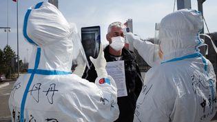 Des employés portant des combinaisons de protection contre le coronavirus vérifient la température d'un conducteur à un poste de contrôle douanier à la frontière avec la Russie à Suifenhe, dans la province du Heilongjiang(Chine), le 1er mai 2020. (AFP)
