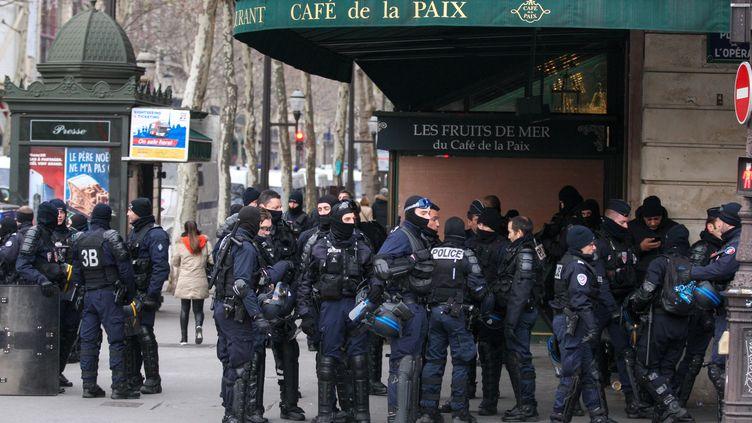 """Des policiers devant le Café de la Paix, place de l'Opéra, à Paris, lors d'une journée de mobilisation des """"gilets jaunes"""", le 15décembre 2018. (MICHEL STOUPAK / NURPHOTO / AFP)"""