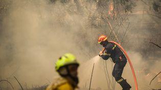 Les pompiers luttent contre les flammes à Athènes (Grèce), le 7 août 2021. (DIMITRIS LAMPROPOULOS / ANADOLU AGENCY / AFP)