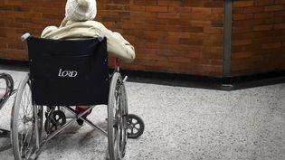 Une personne âgée en fauteuil roulant devant un mur. (RAUL ARBOLEDA / AFP)