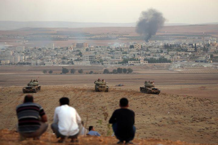 Des réfugiés kurdes observent les combats à Kobani depuis la Turquie, le 9 octobre 2014 à Suruc (Turquie). (IBRAHIM ERIKAN / ANADOLU AGENCY / AFP)