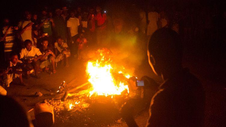 Des personnes prennent en photo le corps d'un Malgache en train de brûler le 3 octobre 13 sur l'île de Nosy Be. Il était soupçonné d'avoir participé à un trafic d'organes sur un enfant de 8 ans, retrouvé mort. (BILAL TARABEY / AFP)