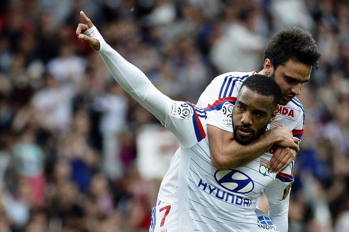 Le buteur lyonnais Alexandre Lacazette est félicité par son équipier Clément Grenier, lors du match Lyon-Evian, le 2 mai 2015. (JEFF PACHOUD / AFP)
