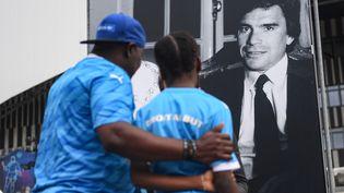 Des Marseillais se recueillent devant une photo en noir et blanc de Bernard Tapie, installée devant le Vélodrome (Bouches-du-Rhône), le 3 octobre 2021. (CLEMENT MAHOUDEAU / AFP)