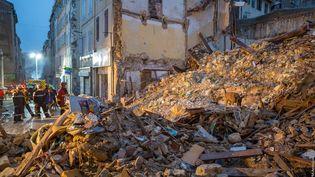 Des pompiers et unchien renifleur recherchent d'éventuelles victimes dans les décombres des immeubles effondrés, rue d'Aubagne à Marseille, le 6 novembre 2018. (LOIC AEDO / BMPM / AFP)