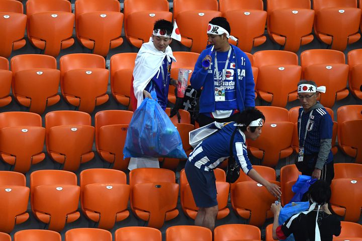 Les supporters du Japon ramassent les déchets à la fin du match opposant l'archipel au Sénégal lors des phases de groupe, lors du Mondial de football, en Russie en 2018. (ANNE-CHRISTINE POUJOULAT / AFP)