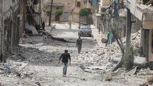 Des habitants marchent dans les ruines après une frappe aérienne sur un quartier d'Alep (Syrie) tenu par les rebelles, le 3 mai 2016. (ABDALRHMAN ISMAIL / REUTERS)