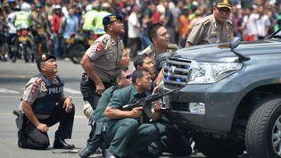 La police prend position derrière un véhicule après une série d'explosions dans le centre de Jakarta (Indonésie), le 14 janvier 2016. (BAY ISMOYO / AFP)