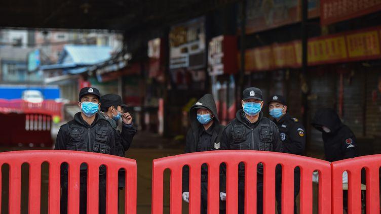 Des militaires gardent le marché aux poissons d'où serait partie l'épidémie de coronavirus, samedi 25 janvier 2020. (HECTOR RETAMAL / AFP)
