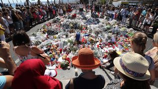 Des personnes se recueillent, le 17 juillet 2016 à Nice (Alpes-Maritimes), devant des fleurs et des bougies déposées en hommage aux victimes de l'attentat du 14-Juillet. (VALERY HACHE / AFP)