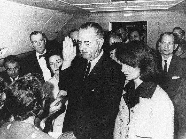 A côté de Jackie Kennedy (à droite), le vice-président américain Lyndon Johnson prête serment dans Air Force One, le 22 novembre 1963, 98 minutes après l'assassinat du président John F.Kennedy à Dallas. (CECIL STOUGHTON-WH PHOTOGRAPHS / JFK PRESIDENTIAL LIBRARY / AFP)
