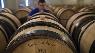 Un employé contrôle les barriques de vin dans le cellier des Hospices de Beaune (Côte-d'Or), le 21 octobre 2014. Une cité des vins de Bourgogne est prévue dans la ville à l'horizon 2017. (PHILIPPE DESMAZES / AFP)