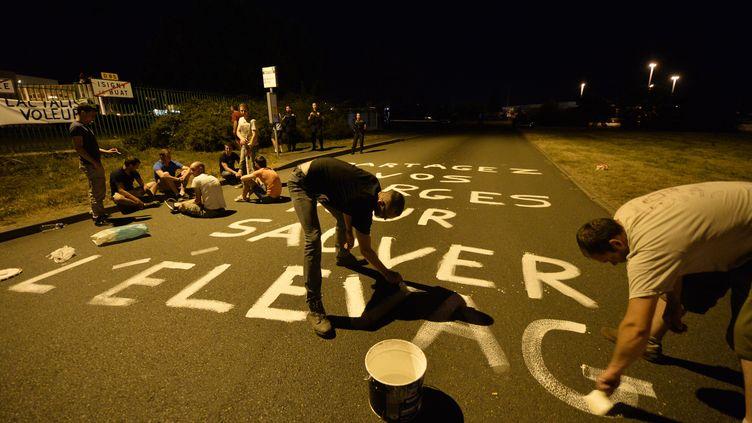 """Des producteurs de lait écrivent un slogan (""""partagez vos marges pour sauver l'élevage"""") sur la routed'accès à l'usine Lactalis en Mayenne, dans la nuit du jeudi 25 au vendredi 26 août 2016. (JEAN-FRANCOIS MONIER / AFP)"""