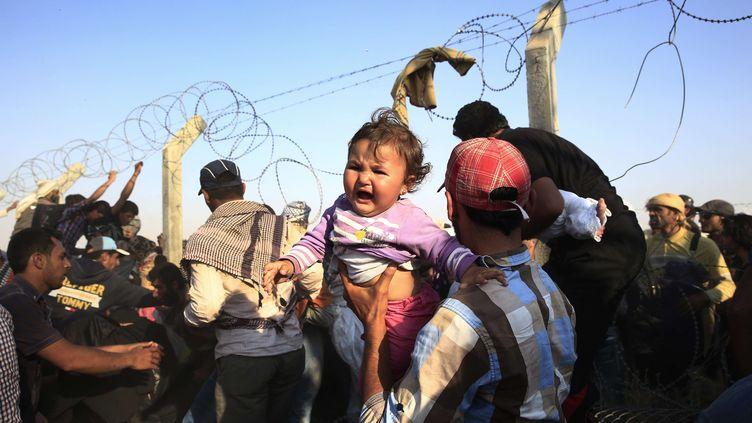 Des familles syriennes tentent de passer la frontière avec la Turquie pour fuir leur pays,le 14 juin 2015à Akcakale (Turquie). (LEFTERIS PITARAKIS / AP / SIPA)