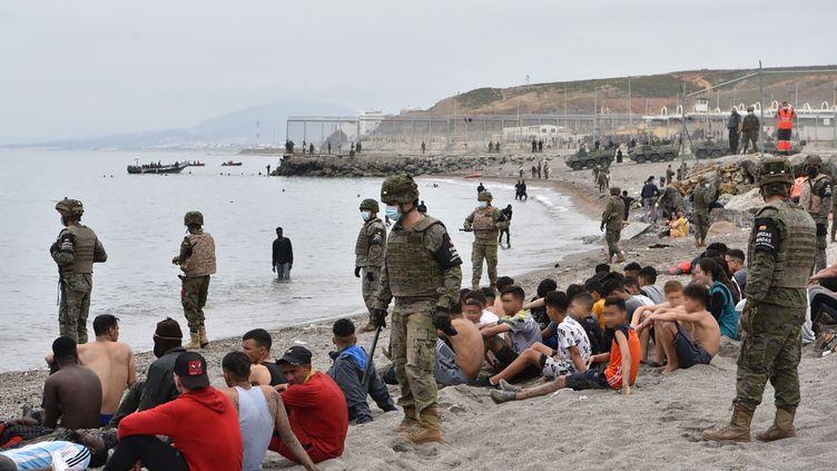 Des migrants, entourés de soldats espagnols, sur une plage de l'enclave de Ceuta (Espagne), le 18 mai 2021. (ANTONIO SEMPERE / AFP)