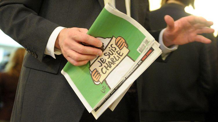 """Un""""Charlie Hebdo"""" dans les mains d'un client, au kiosque de l'Assemblée nationale, à Paris (14 janvier 2015)  (Éric Piermont / AFP)"""