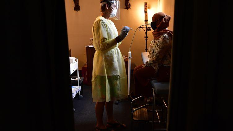 Une infirmière s'apprête à réaliser un prélèvement nasopharyngé dans une église d'Anvers (Belgique) transformée en centre de dépistage du Covid-19. (JOHN THYS / AFP)