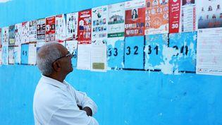 Un Tunisien observe les affiches électorales avec les législatives, à Tunis, le 21 octobre 2014. ( CITIZENSIDE / AFP)