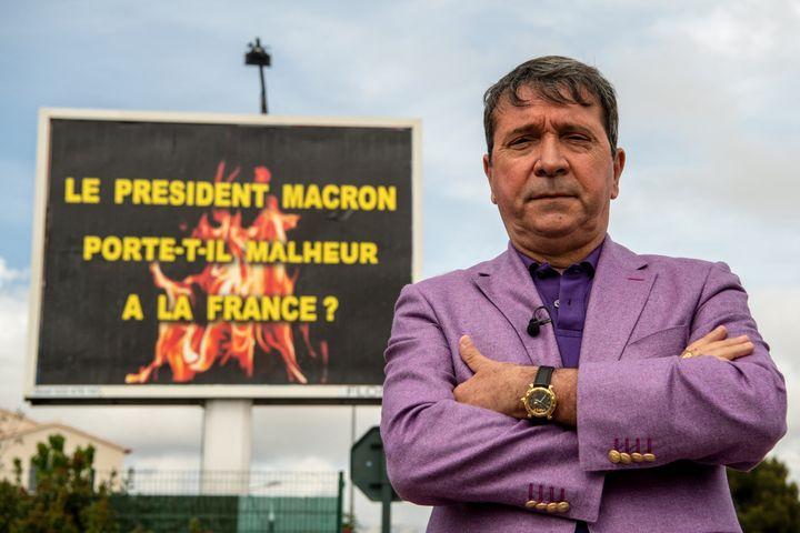 Michel-Ange Flori devant l'un de ses panneaux publicitaires à La-Seyne-sur-Mer (Var), le 25 avril 2019. (CHRISTOPHE SIMON / AFP)