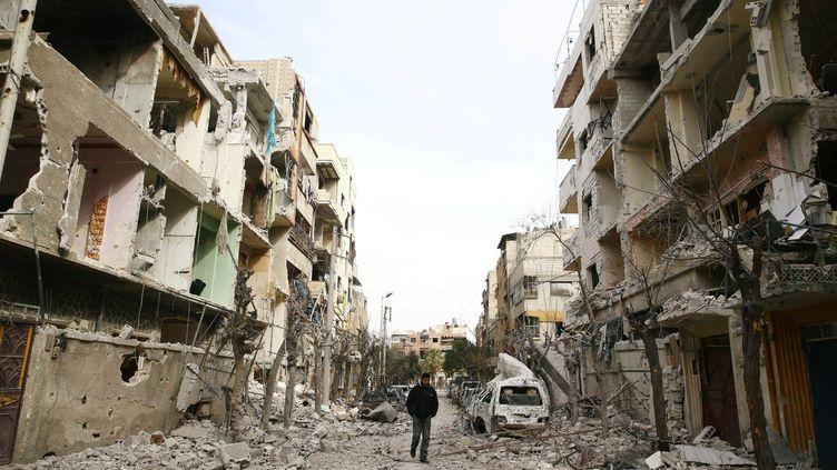 Un homme dans une rue dévastée de la Ghouta orientale, près de Damas, la capitale syrienne, le 25 février 2018. (BASSAM KHABIEH / REUTERS)