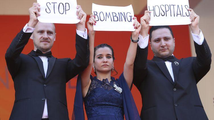 """L'équipe du film """"Pour Sama"""", les coréalisateursEdward Watts et Waad Al-Kateab, et, à droite et Hamza Al-Kateab, médecin et époux de cette dernière, brandissent le message """"Cessez de bombarder des hôpitaux""""avant la projection dufilm """"Les Misérables""""au Festival de Cannes, le 15 mai 2019 (VALERY HACHE / AFP)"""