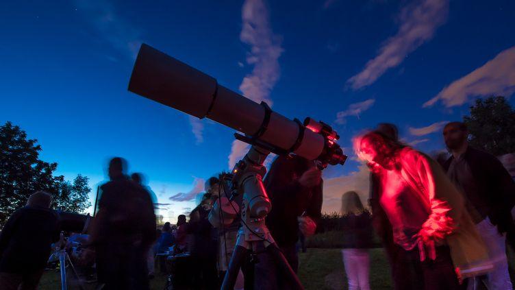 """Des personnes du Club astronomique de la région lilloise scrutent le ciel le 2 août 2014, à l'occasion de la """"Nuit des étoiles"""". (PHILIPPE HUGUEN / AFP)"""