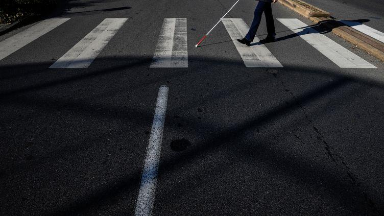 Un aveugle traversant un passage piéton (illustration). (JEFF PACHOUD / AFP)