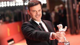 """Le réalisateur français, François Ozon récompensé pour son film """"Grâce à Dieu"""" lors du festival du film de Berlin, le 16 février 2019. (GREGOR FISCHER / DPA / AFP)"""