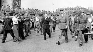 Une photo prise le 26 août 1944, le jour après la Libération de Paris. Lesgénéraux Français deGaulleet Leclerc marchent en bas des Champs Elysees pour rejoindre la cathédrale de Notre-Dame. (ARCHIVES / AFP)
