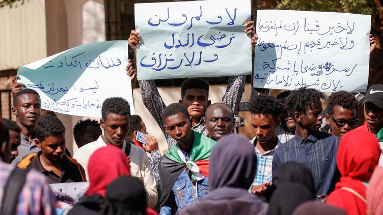 """Des Soudanais manifestent devant le ministère des Affaires étrangères à Khartoum, la capitale du Soudan, le 28 janvier 2020. Ils portent des affiches sur lesquelles on peut lire : """"Nous refusons l'humiliation"""", """"Nous ne sommes pas des mercenaires"""". (ASHRAF SHAZLY / AFP)"""