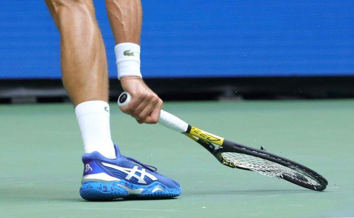 Novak Djokovic brise sa raquette lors de la finale de l'US Open face au Russe Daniil Medvedev, lundi 13 septembre 2021. (KENA BETANCUR / AFP)