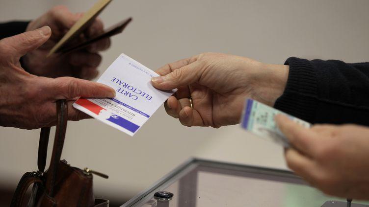 Une électrice présente sa carte électorale, le 29 mars 2015 au Grand-Quevilly (Seine-Maritime). (CHARLY TRIBALLEAU / AFP)