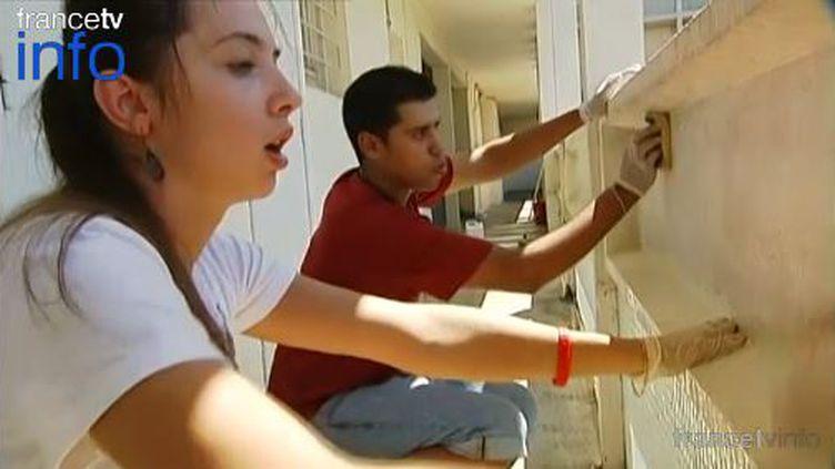 Capture d'écran d'un reportage de France 2 sur de jeunes étrangers passant leurs vacances dans une cité HLM de Clermont-Ferrand (Puy-de-Dôme) pour faire du bénévolat. ( FRANCE 2 / FRANCETV INFO)