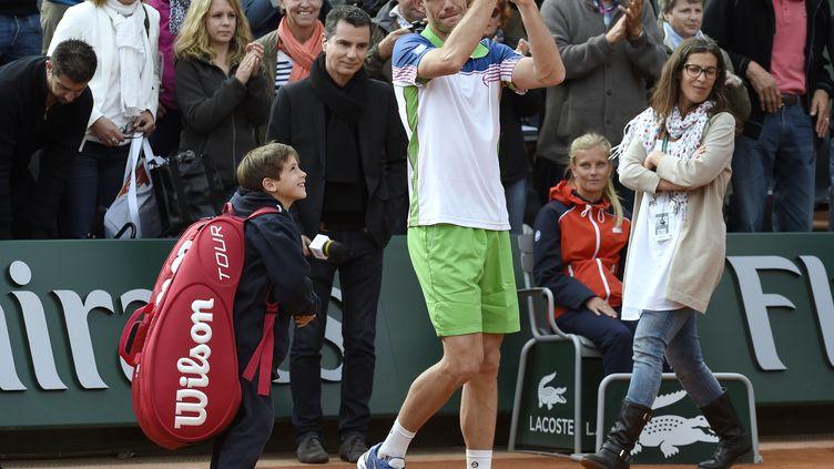 Michaël Llodra, 34 ans, et son fils, après sa défaite et son dernier match à Roland-Garros, le 27 mai 2014. (PASCAL GUYOT / AFP)