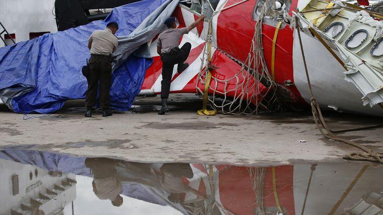 Des policiers indonésiens inspectent une partie de l'avion d'AirAsia, qui s'était abîmé en mer le 28 décembre 2014. (DARREN WHITESIDE / REUTERS)
