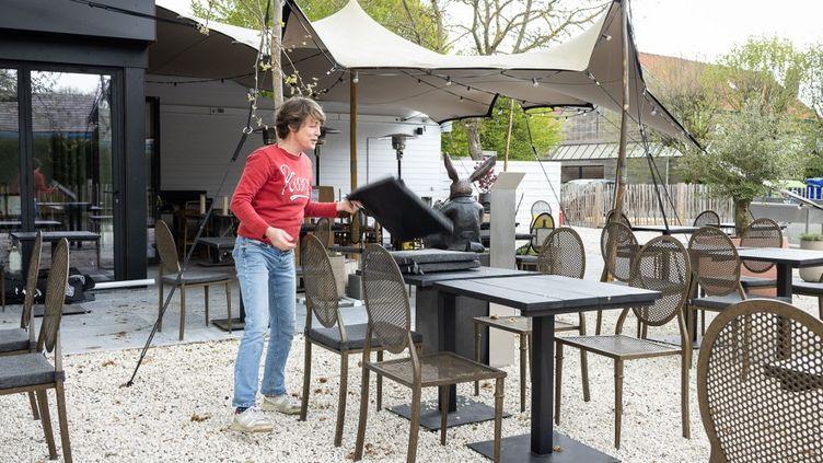 Un restaurateur prépare sa terrasse,le 6 mai 2021, en vue de la réouverture le 19. (JAMES ARTHUR GEKIERE / BELGA MAG)